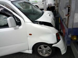トラックの荷台部分に衝突した白い軽ワゴン車