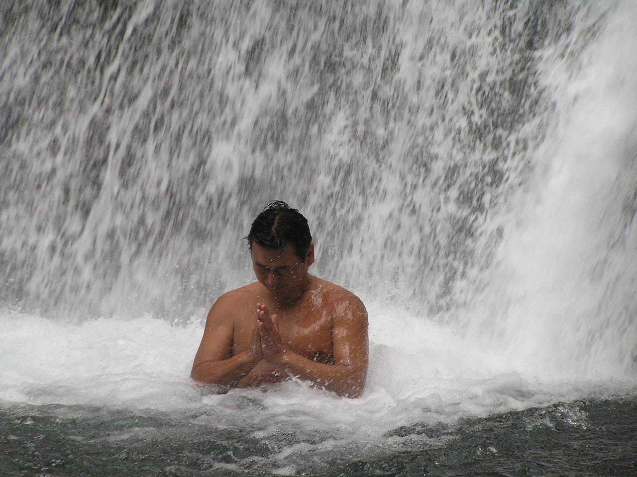 裸で滝に打たれる男性