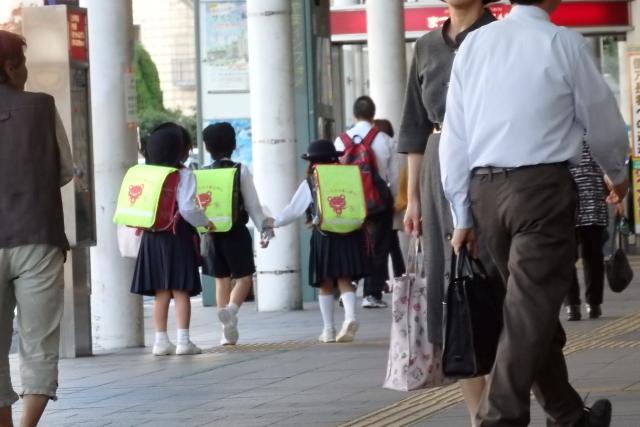 商店街の中を3人の班になって下校する小学生