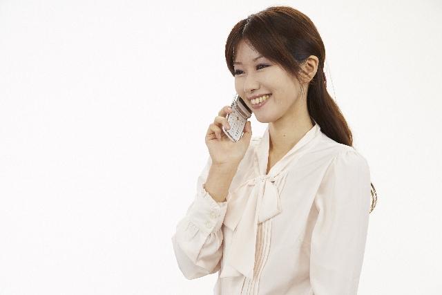 保護者と携帯電話で会話をする女性教員