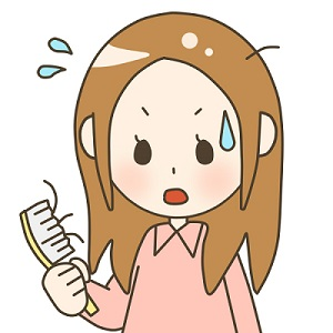 櫛で髪を解いたら抜け毛が酷くて焦るロングヘアーの女性