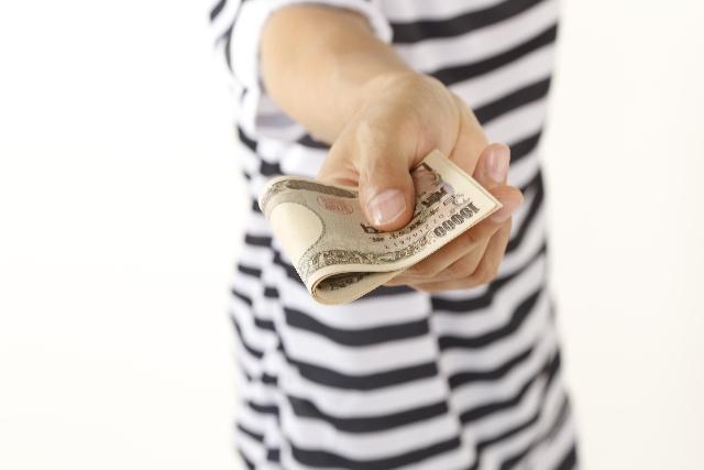 1万円札を差し出す男性の手