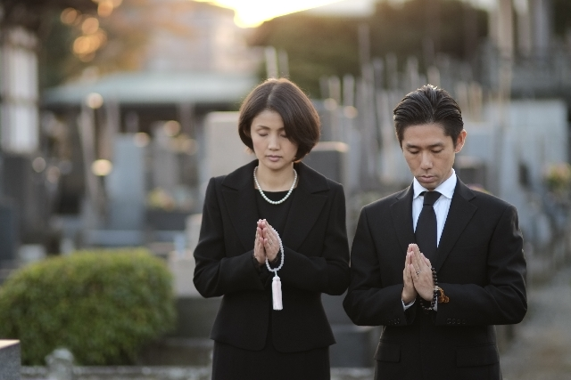喪服で数珠を持って故人の冥福を祈る夫婦