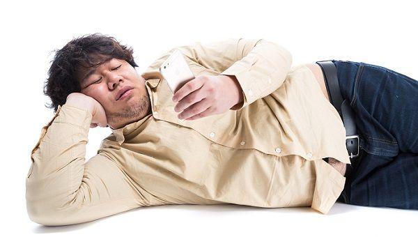 寝転がってスマホを触る太った男性