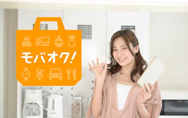 台所でタブレットを使いモバオクを楽しむ美人主婦