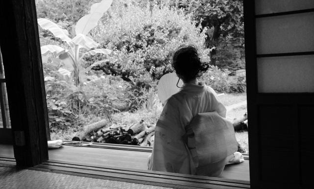 縁側で庭を眺める着物日本人女性(白黒)